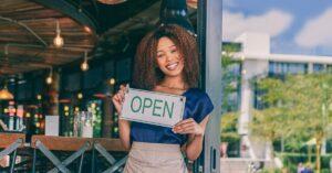 Business Representative displays open business sign